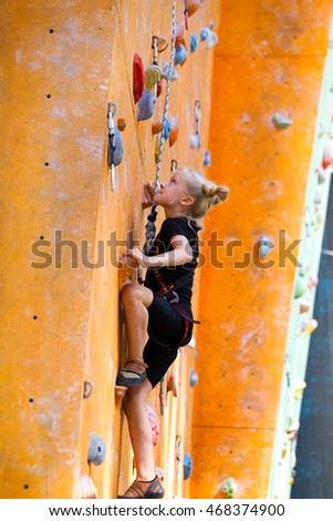bouldering, little girl climbing up the wall