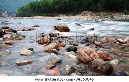 Boulders and rock pebble in the flowing creek water.