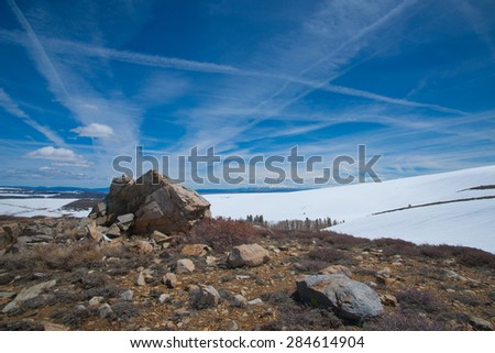 Boulders and rocks on a snowy peak in the high Sierra Nevada mountains. - stock photo