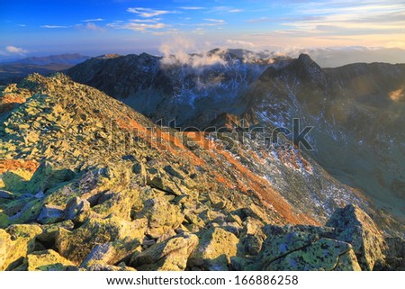 Boulders and vegetation scattered on the mountain ridge at sunset - stock photo