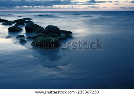 Boulders covered with moss on the sandy coast - stock photo