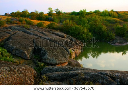Boulders, moss,  water reflection, morning sky. trees. - stock photo