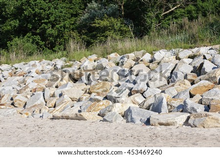Boulders on the beach placed to protect the dunes from the ravages of the sea waves by the Baltic Sea in Kolobrzeg - stock photo