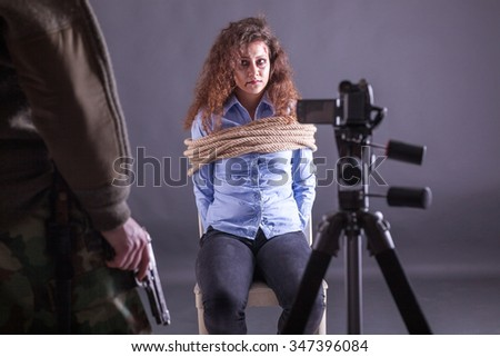 bound beaten women, in the hands of kidnappers in front of camera - stock photo