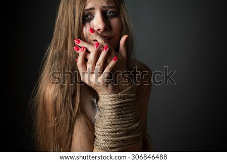 Bound girl on a dark background. Victim - stock photo