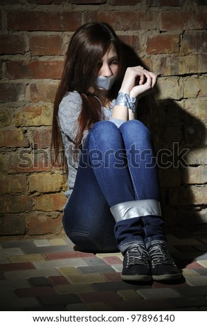 Bound girl sitting next to stone wall