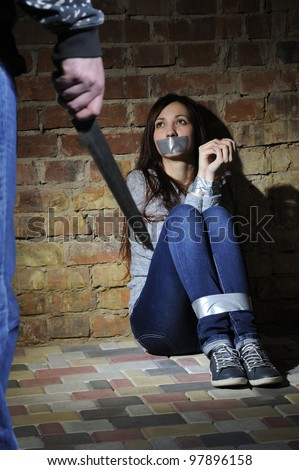 Bound girl sitting next to stone wall. Man with  knife approaching her. - stock photo