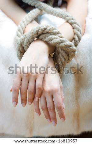 Bound hands of young beautiful woman - stock photo