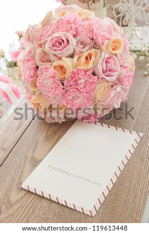 Bouquet and wedding card on wooden table - stock photo