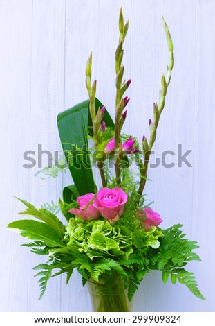 Bouquet composition with pink rose and gladiolus on black wooden background - stock photo