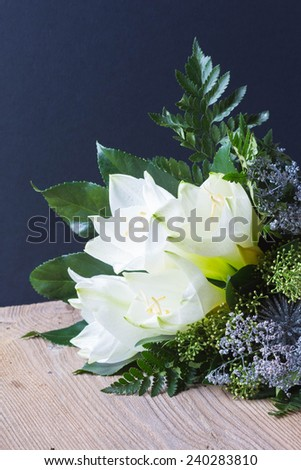bouquet composition with white amaryllis on wooden and black background