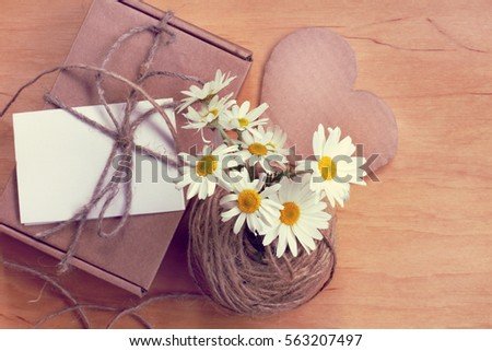bouquet daisies on a background of heart and gift top view / congratulations on the occasion