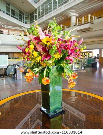 Bouquet, flowers in the vase on the table in the lobby of the big luxury hotel in Vancouver, Canada. - stock photo