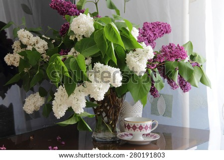 Bouquet from branches of a white and lilac lilac and a cup with tea