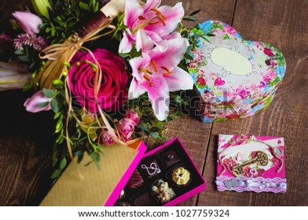 Bouquet from different colors with a box of sweets on a wooden table. Gift set on St. Valentine's Day