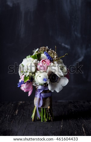 Bouquet from pink tulips, violet grape hyacinths, white anemones, violet veronica and white buttercup with violet ribbon standing on black wood with blackboard in the background