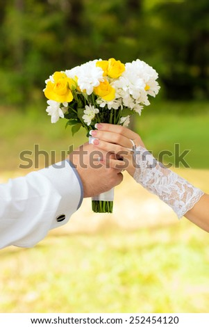 Bouquet keep the bride and groom on the background of nature - stock photo
