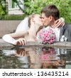 bouquet lies on the edge of the fountain on the background of kissing the newlyweds - stock photo