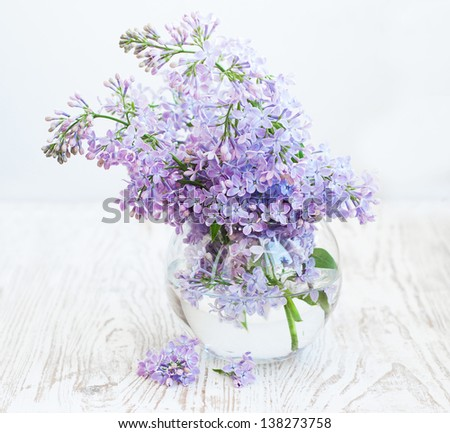 Bouquet of a lilac in a  vase  on a wooden  background - stock photo
