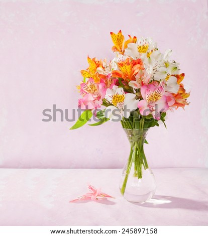 Bouquet of Alstroemeria in a transparent glass vase on light pink background - stock photo