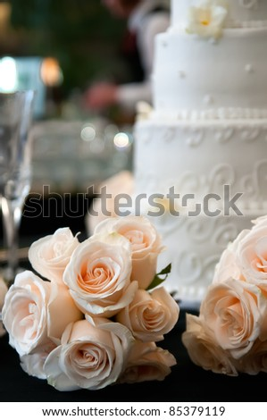 Bouquet of apricot roses with a white wedding cake in the background - stock photo