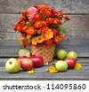 Bouquet of autumn flowers is with apples on an old wooden background - stock photo