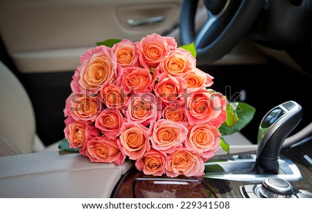 Bouquet of beautiful elegant pink roses in luxury car, express feeling. Composition for a romance or anniversary - stock photo