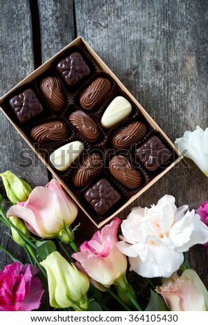 bouquet of beautiful flowers and chocolate on wooden surface - stock photo