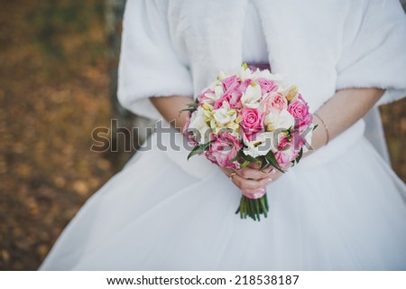 Bouquet of beautiful flowers in hands of the bride.