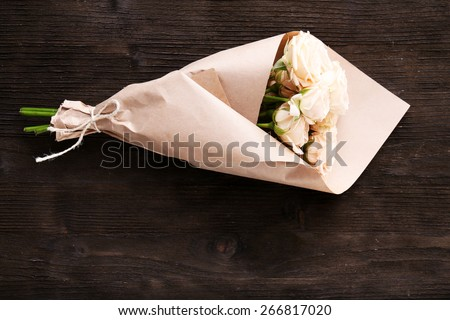Bouquet of beautiful fresh roses wrapped in paper on wooden background - stock photo