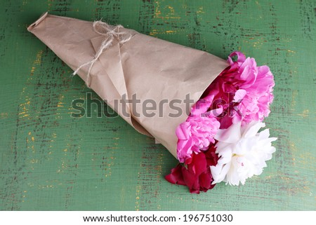 Bouquet of beautiful peonies on wooden background