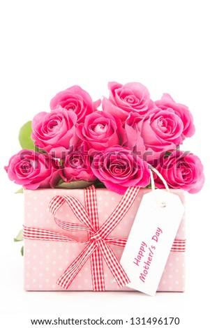 Bouquet of beautiful pink roses next to a pink gift with a happy mothers day card on white background close up - stock photo