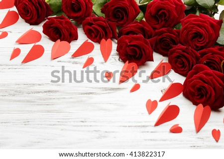 Bouquet of beautiful red roses with small hearts on wooden background