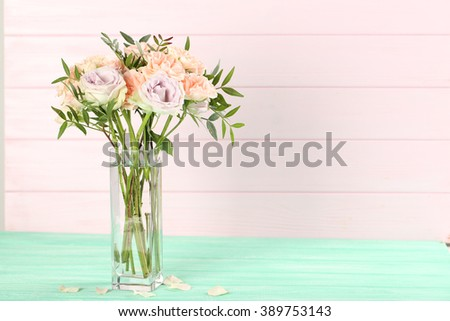 Bouquet of beautiful roses on a mint wooden table