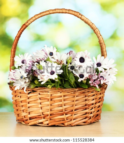 bouquet of beautiful summer flowers in basket, on green background
