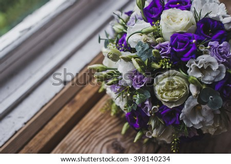 Bouquet of beige purple flowers on the windowsill.
