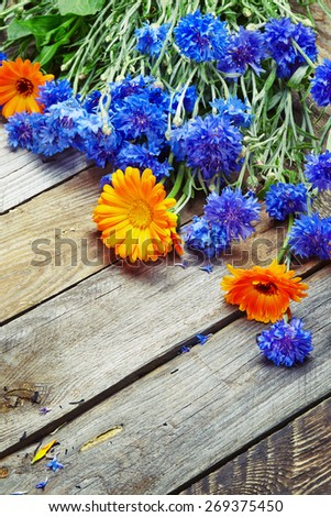 bouquet of blue cornflowers and calendula on vintage wooden board  - stock photo