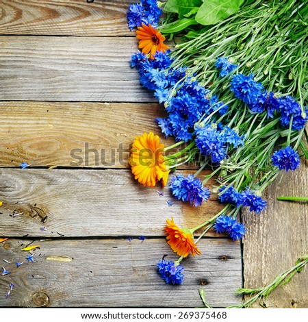 bouquet of blue cornflowers and calendula on wooden board  - stock photo