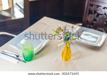 Bouquet of bright wildflowers in a vase on a kitchen table