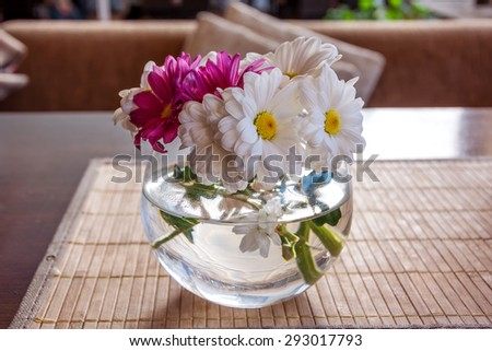 Bouquet of camomile white and vinous flowers in glass vase on the table