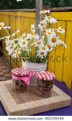 Bouquet of camomiles and banks with a granola - stock photo
