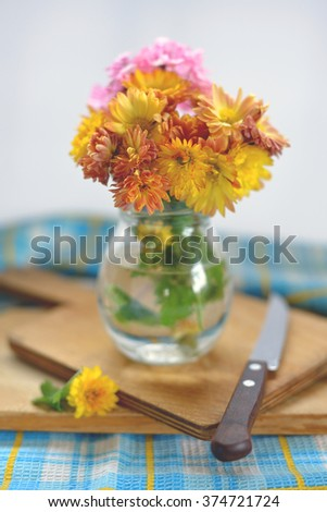 Bouquet of chrysanthemum in a glass bottle on a wooden cutting Board - stock photo