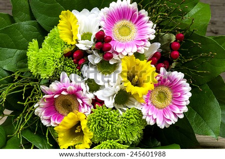 Bouquet of colorful flower with a wooden background - stock photo