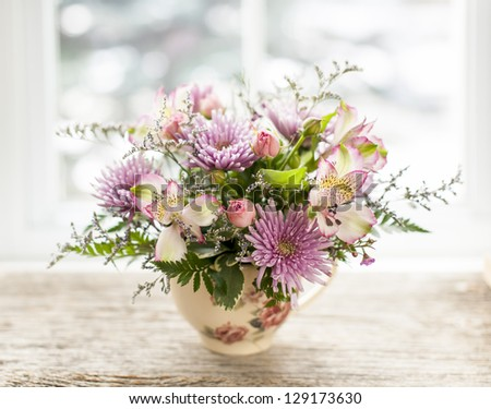 Bouquet of colorful flowers arranged in small vase - stock photo