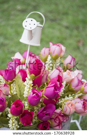 Bouquet of colorful roses with a small watering pot - stock photo