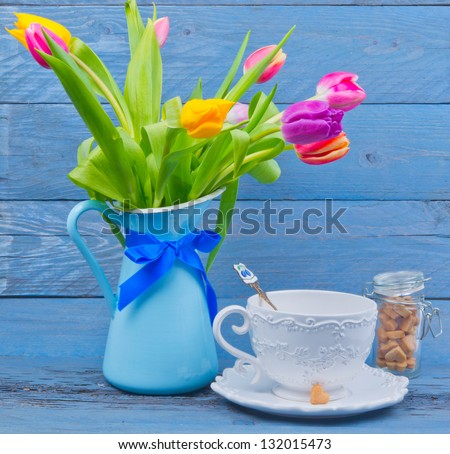 Bouquet of colorful tulips in a blue jug, next cup of tea on blue wooden table