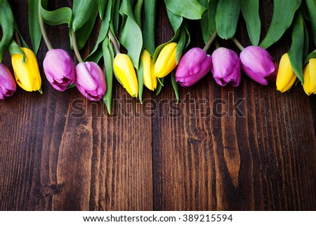 bouquet of colorful tulips on rustic wooden board, easter decoration - stock photo