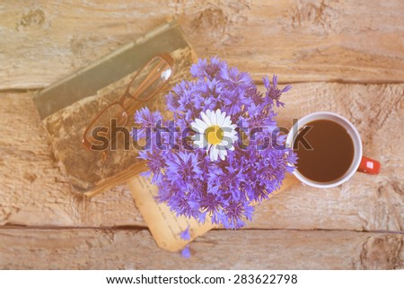 Bouquet of cornflowers and chamomile on the table. A vase of flowers. A Cup of coffee on the table, wooden table, old book, glasses and a bouquet. Sunlight, sunbeam, morning. Summer morning. Vintage. - stock photo