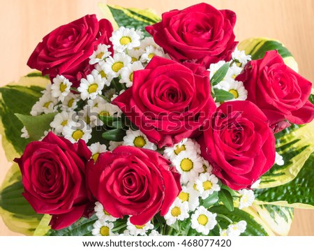 bouquet of daisies and red roses