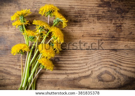 Bouquet of dandelions on brown wood table with empty copy-space for text